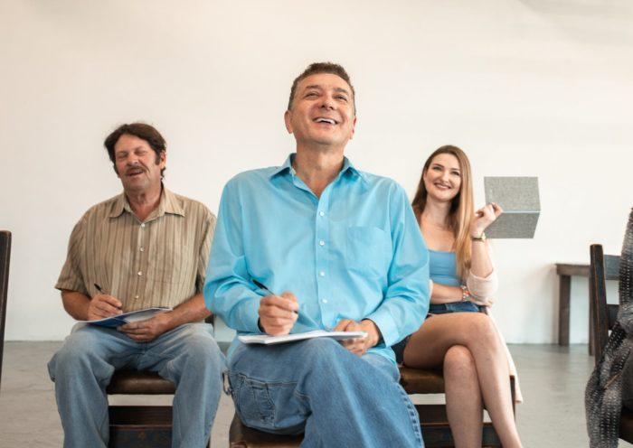 man in blue dress shirt sitting beside woman in brown cardigan